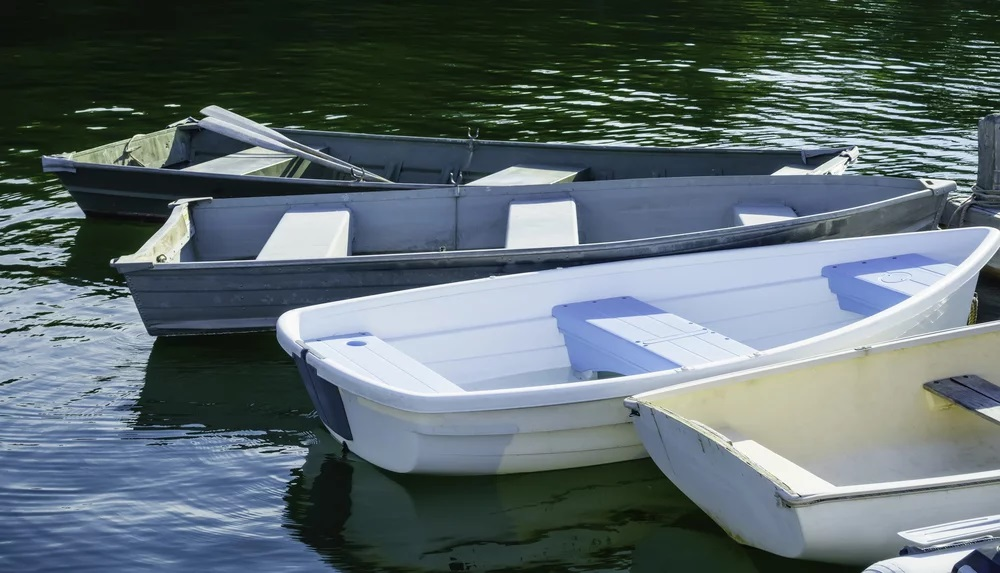 Four rowboats, one with a pair of oars, tied up to dock in Maine